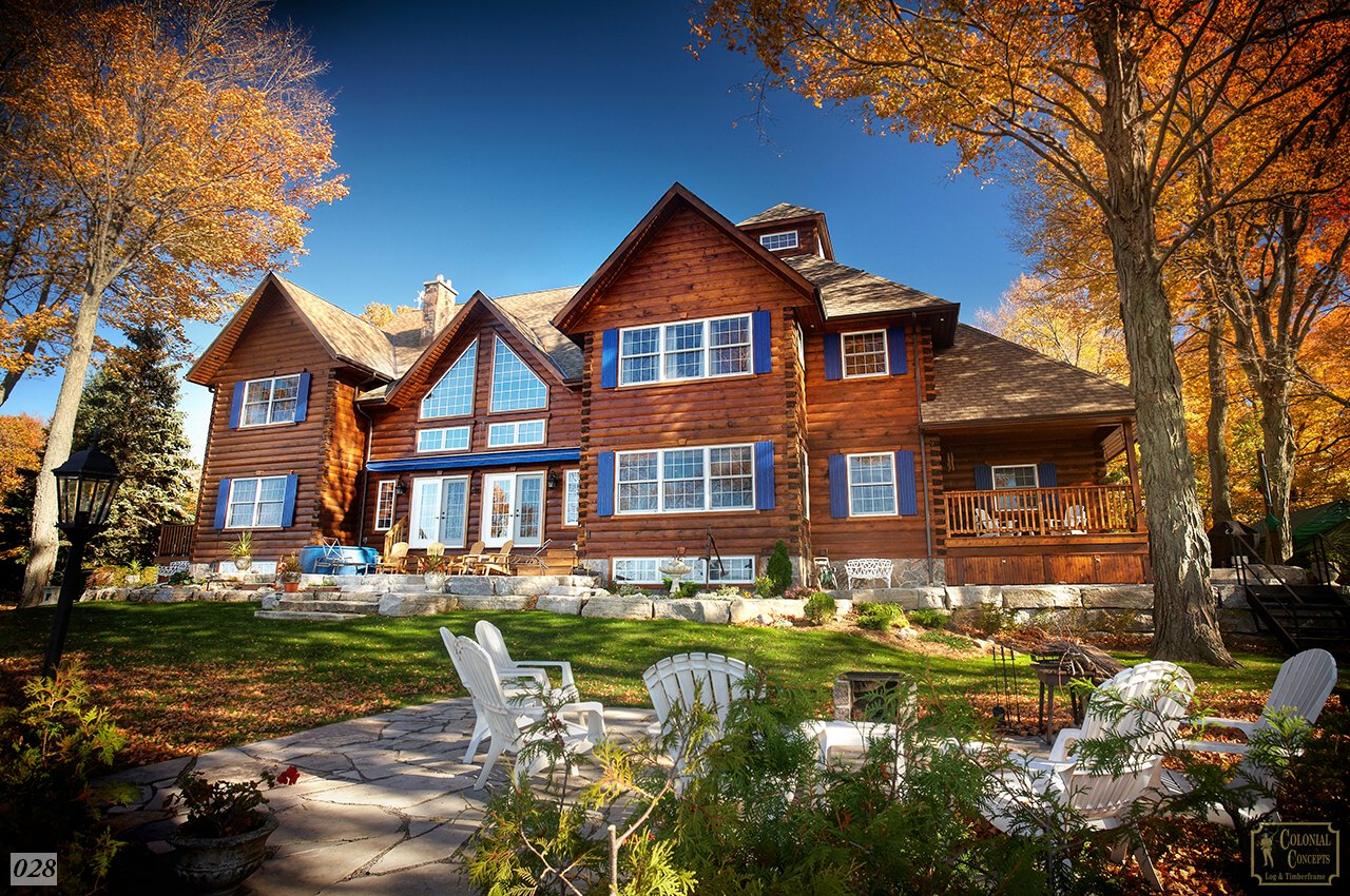 Log home, large, with blue shutters in the fall