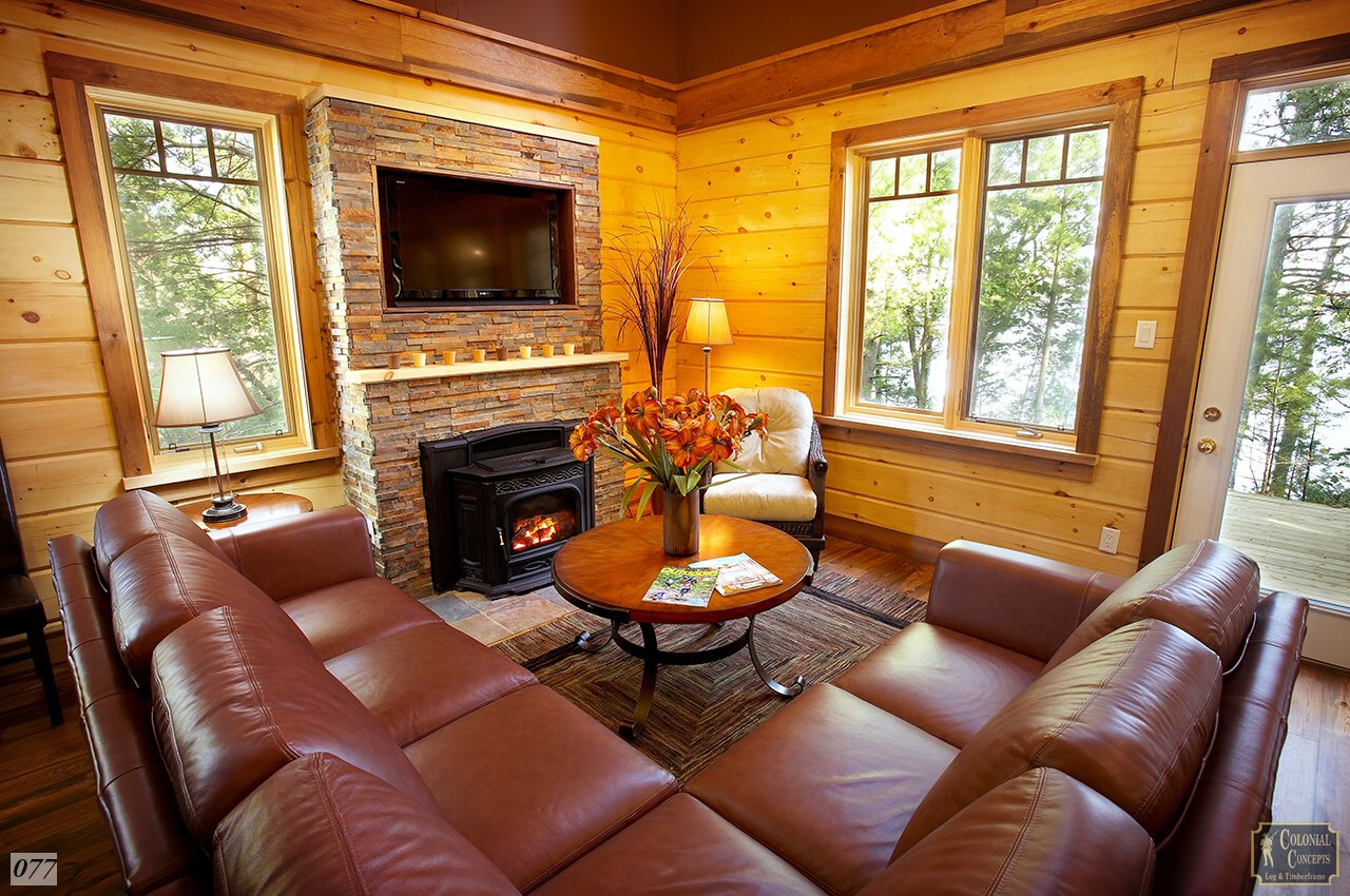 log home with stone fireplace and leather couches